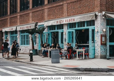 New York, Usa - May 28, 2018: People Sitting At The Outdoor Tables Of Pizza Beach Restaurant In Lowe