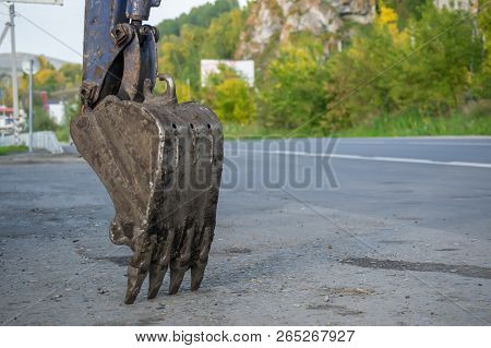 The Dirty Bucket Of The Excavator For Digging Of Holes Is About The Carriageway Of The Highway Near