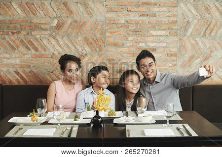 Happy Asian Family Photographing Themselves At The Served Table At Restaurant