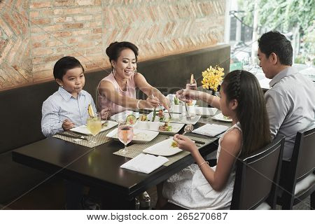 Asian Family Sitting At The Table And Have Dinner Together At Restaurant