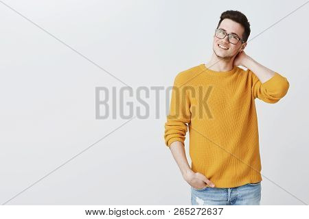 Indoor Shot Of Charming Nice And Handsome Young Guy In Glasses And Yellow Sweater Touching Back Of N