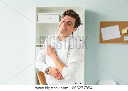 Business People, Fool And Joke Concept - Young Handsome Man In Suit Having Fun In The Office