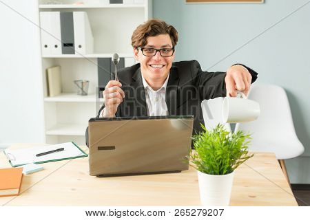 Office, Humor, Joke And Business People Concept - Handsome Man Working In Office, Watering Potted Pl