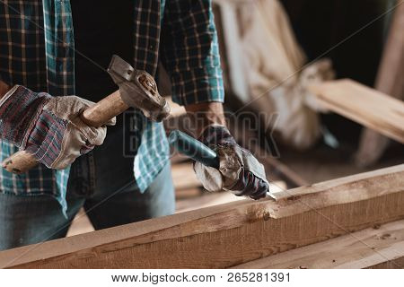 Joiner At Work In A Woodworking Workshop. Carpenter With A Hammer And Chisel Handles Wood. Home Work