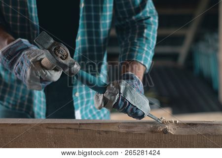 Joiner at work in a woodworking workshop. Carpenter with a hammer and chisel handles wood. Home workshop, DIY poster