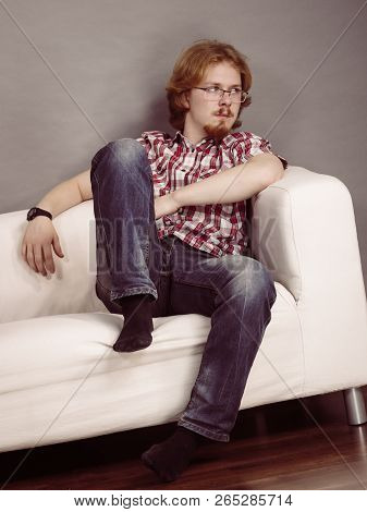 Thinking Guy Sitting On Sofa. Young Ginger Redhead Man Having Contemplation Gesturing With Hand.