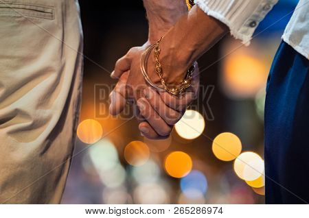 Closeup of loving couple holding hands while walking outdoors at night. Mature man and fashionable woman holding hands on street. Hands of senior married couple joined together, romantic atmosphere.