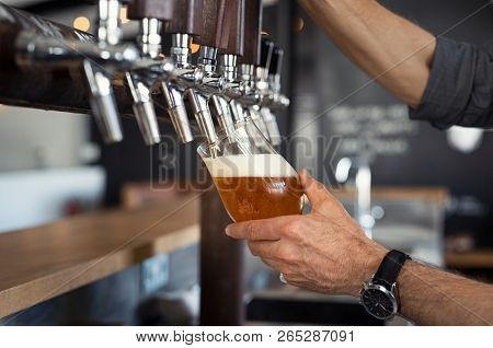Hand of bartender pouring a large lager beer in tap. Closeup of hand serving beer in glass using tap. Close up of barman hand at beer tap pouring an amber draught beer at pub.