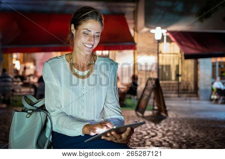 Beautiful mature woman using digital tablet while sitting on bench outside restaurant. Smiling latin lady surfing the net on digital tablet at night on city street after work. Happy lady reading ebook