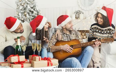New Year Celebration Party. Man Playing On Guitar For Friends At Christmas House Party, Copy Space