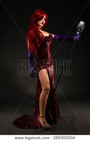 Full-length Portrait Of Young Romantic Redhead Woman With Very Long Hair In Red Dress With Microphon
