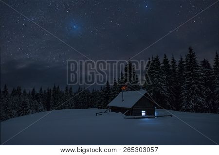 Wooden Cabin Under Stars. Lights Shines Through The Window From Inside Of The House. Night Landscape