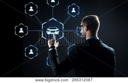 business, rental service and future technology concept - close up of businessman with virtual hologram of car sharing over black background