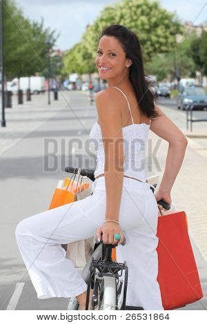 Back shot of a young woman clothes shopping on a bicycle