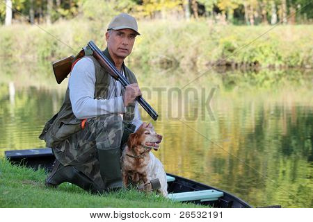 A hunter and his dog by a river.