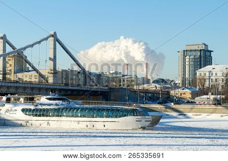 Moscow, Russia - January 8, 2017: Pleasure Boat Sailing On A Frozen River Under The Bridge Metal Str