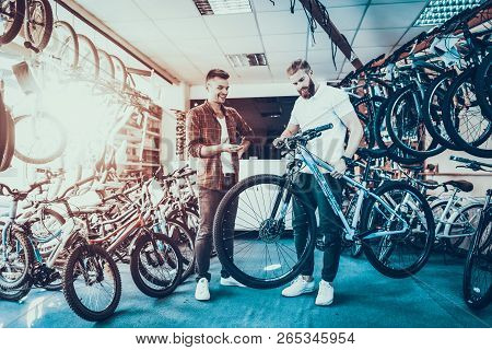 Consultant Shows Bicycle To Client In Sport Shop. Portrait Of Young Shop Assistant Wearing White T-s