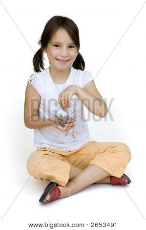 Little Girl Putting Money Into The Piggy Bank