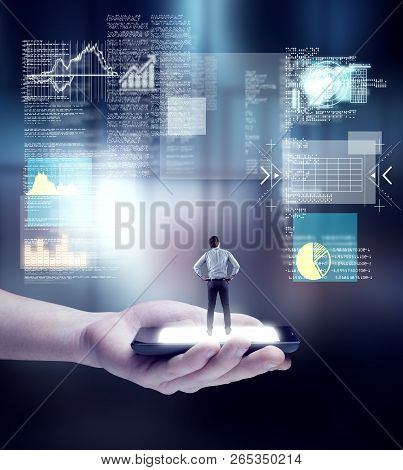 Hand Holding A Smartphone With Businessman Standing And Analyze A Digital Screen With Of Codes And I