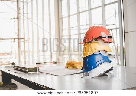 Yellow,white, Blue, Orange Helmet Safety Engineer For Project Engineering.conceptual Images Of Const