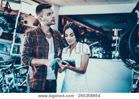 Young Couple Choose Bike Look At Catalog In Shop. Portrait Of Young Female Shop Assistant Wearing Wh