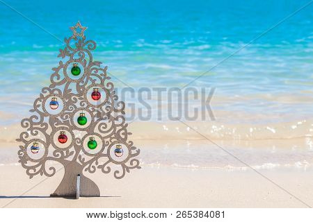 Wood Christmas Tree With Decorations On Sea Coast With White Sand And Clear Blue Water On Phuket Isl