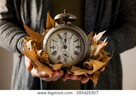 closeup of a young man with an old and rusty alarm clock surrounded by dry leaves in his hands, depicting the end of the summer time and the beginning of autumn