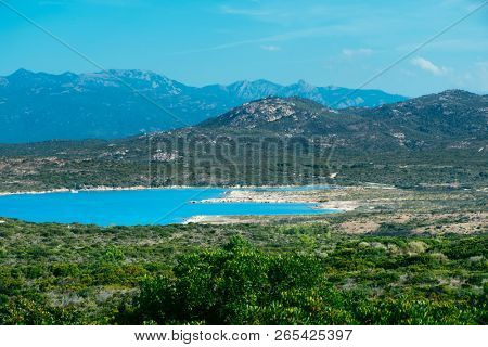 a view over the natural landscape of the Southern coast of Corsica, France, with a calm Mediterranean sea in the center, surrounded by mountains