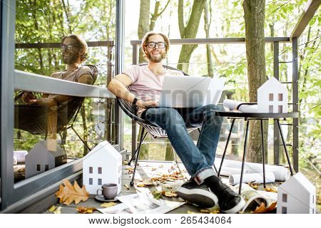 Portrait Of A Creative Man Architect Or Designer Working With Laptop And Drawings Sitting On The Bal