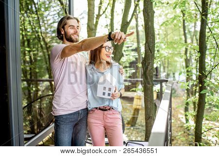 Young Couple Dreaming About Eco House Standing With House Model On The Balcony In The Forest