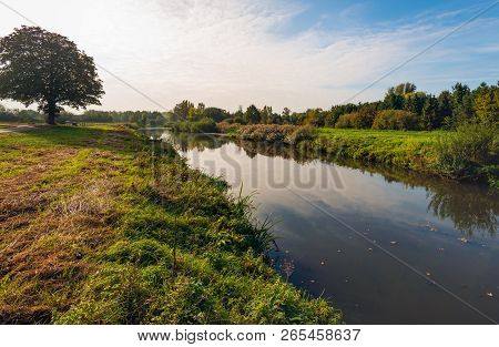 The Narrow Dutch River Mark In The Autumn Season. The Nature Is Already Changing The Colors. The Pho