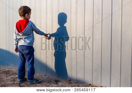 Boy And His Shadow. Lonely Little Child Playing With His Shadow Outside. Imaginary Friend. The Conce