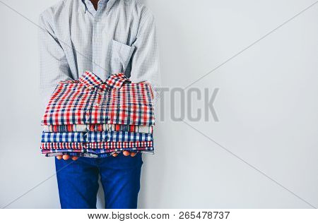 Close Up Stack Of Folded Colorful Plaid Shirt In Hands, Man Holding Folded Clothes In Hands On White