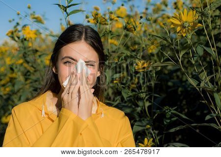 Beautiful Sexy Young Woman Lies On Flowers Background. Young Woman Got Nose Allergy, Flu Sneezing No