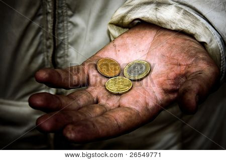 A beggar with some coins on his dirty hands