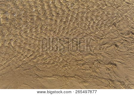 Beautiful sunlit small waves of shallow clear water on the smooth sand