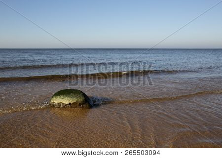Calm Sunny Autumn Day View With Lonely Stone In Cold Baltic Sea Waves