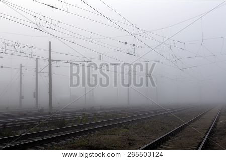 Crossing Railways Fading Away In The Mist In Autumn Morning