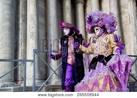 Colorful Pair Carnival Purple-beige Mask And Costume At The Traditional Festival In Venice, Italy
