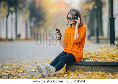 Cute Young Girl Listening Music In Headphones, Urban Style, Stylish Hipster Teen Sitting On A Sidewa