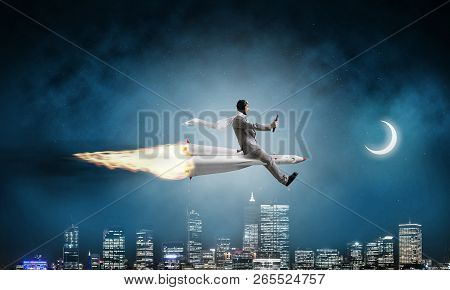 Conceptual Image Of Young Businessman In Suit Flying On Rocket With Night Cityscape And Blue Dark Sk