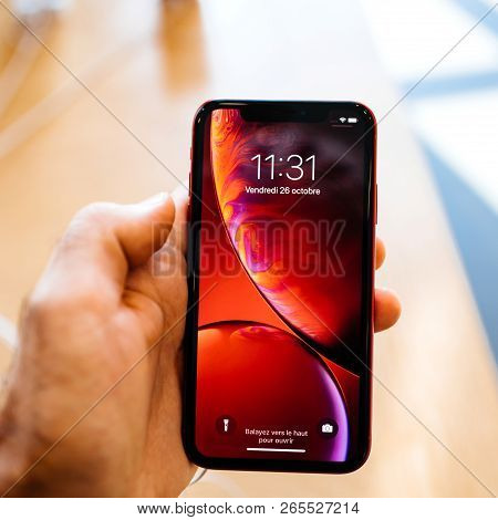 Paris, France - Oct 26, 2018: Man Hand Holding Latest Red Iphone Xr Smartphone In Apple Store Comput