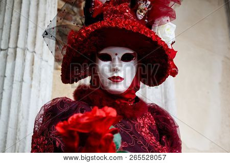 Colorful Carnival Red-bordeaux Mask And Costume At The Traditional Festival In Venice, Italy