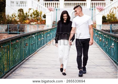 The Girl And The Guy Walk On The Bridge In The Park
