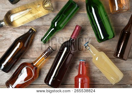 Bottles With Different Alcoholic Drinks On Wooden Background, Flat Lay