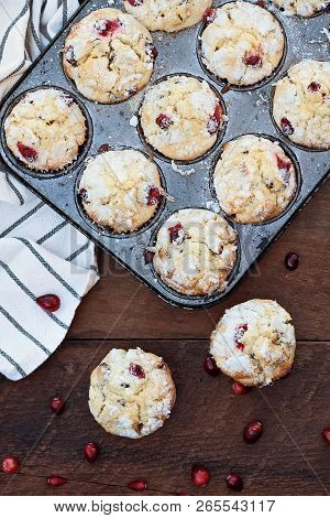 Cranberry Muffins  In A Muffin Tin With Kitchen Towel Over A Rustic Wood  Background With Scattered