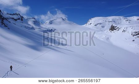 Woman Hiking Into The Winter Wilderness Of The Alps Of Switzerland With Snowshoes On A Beautiful Day