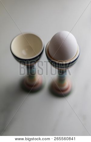 Two Eggcups On A Marble Table With Colorful Stripes And Only One Egg, Litchen