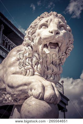 Statue Of A Lion Putting A Paw On A Ball. Classical Marble Lion Sculpture Close-up Outdoor. Face Of