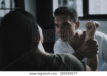 Man Holds Hand Fights And Abuse Woman At Home. Portrait Of Married Couple Sitting On Gray Bed And Ar